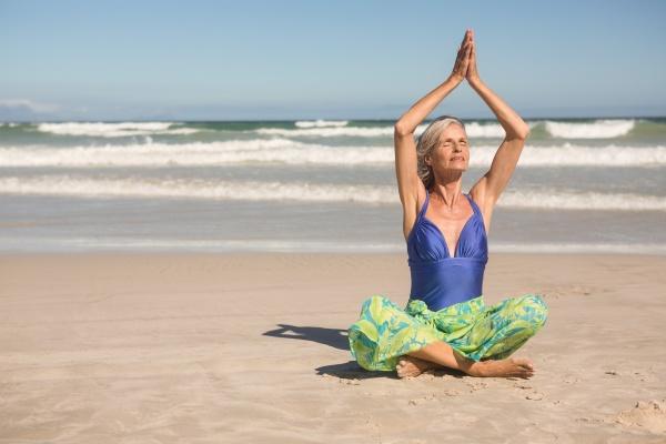 senior woman practising yoga while sitting