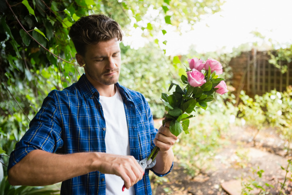 man trimming flowers with pruning shears
