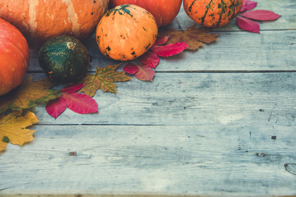 pumpkins and autumn leaves on wooden