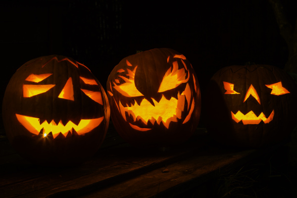 group of candlelit halloween pumpkins against