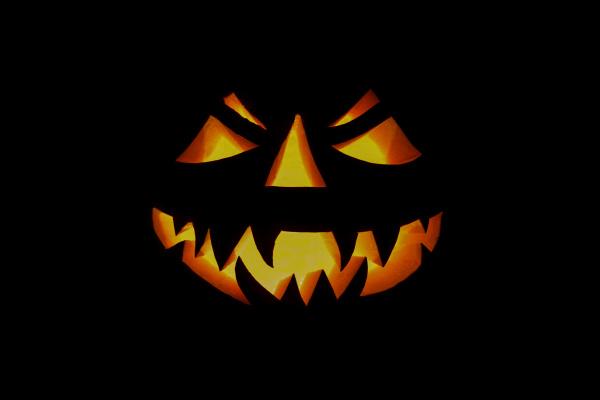 illuminated halloween pumpkin on a black