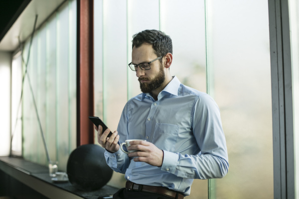 busy businessman in office using smartphone