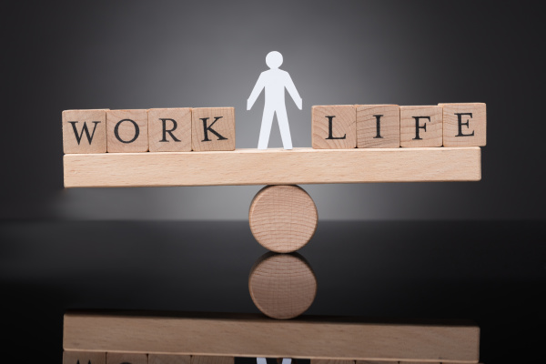 human figure balancing between work and