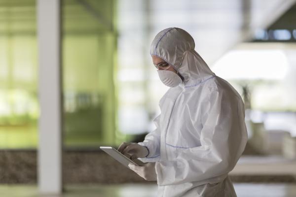scientist in clean suit using digital