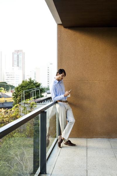 businessman standing on balcony using smartphone