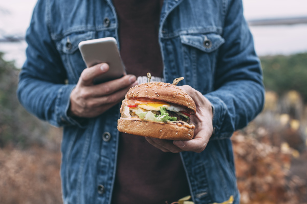 man with burger and smartphone
