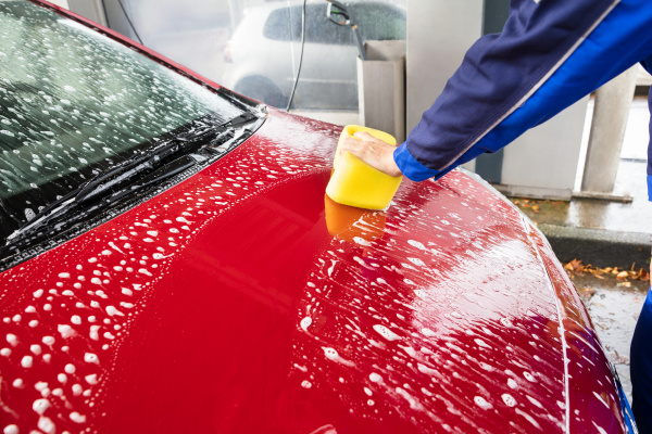 worker s hand washing red car