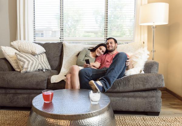 caucasian couple cuddling on sofa watching
