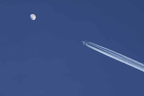 airplane against blue sky with moon
