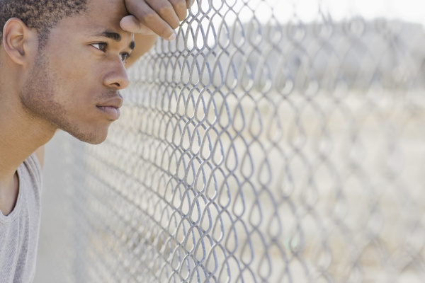 young man leaning against chain link