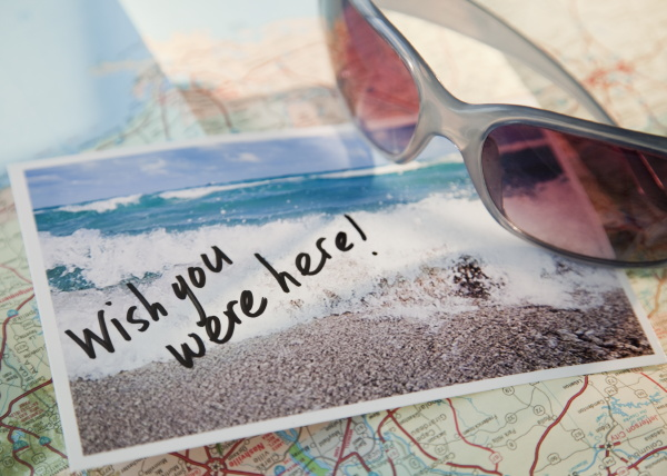close up of sunglasses and postcard