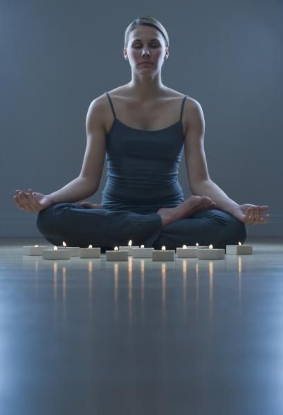 woman meditating next to candles