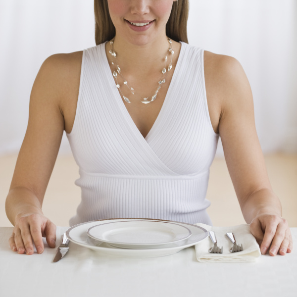 woman sitting at empty place setting