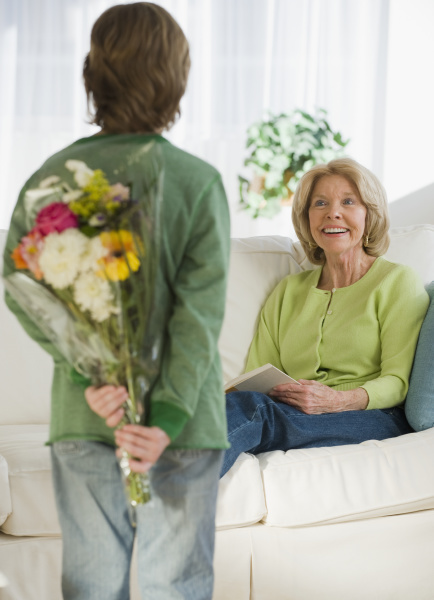 grandson surprising grandmother with flowers