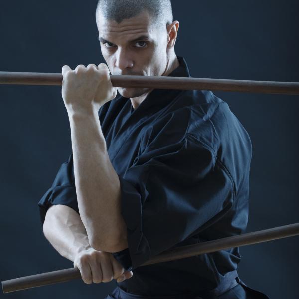 hispanic male holding sticks in fighting