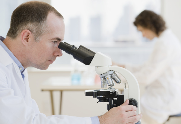 male scientist looking into microscope