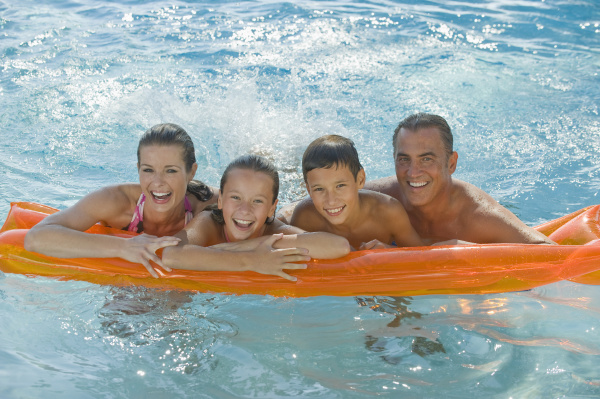 family resting on raft in swimming