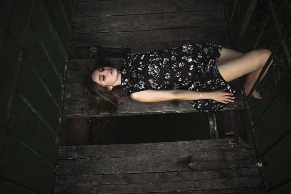 caucasian woman laying on wooden bridge