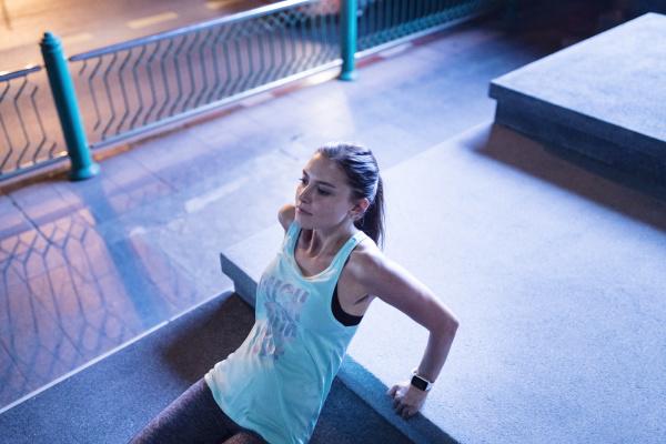 young woman doing reverse pushups in