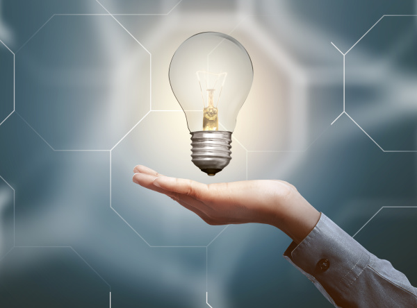 human hands holding light bulb with