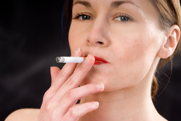 young woman is smoking a cigarette