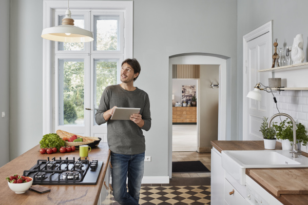 man using tablet in kitchen looking
