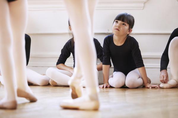 cute girl looking at ballerinas dancing