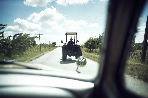 tractor seen through windshield of car
