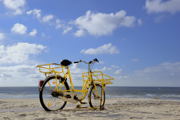 yellow bike stands on the beach
