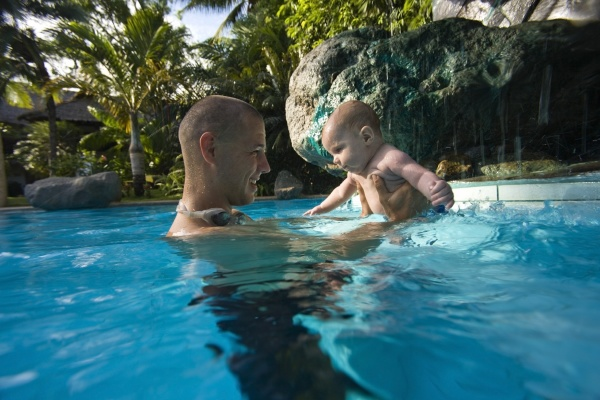 father holding baby in swimming pool