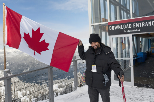 a skiier holds up a canadian