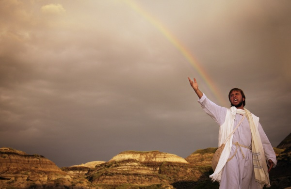 man with outstretched arm rainbow in