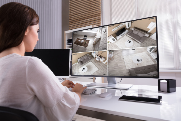 businesswoman monitoring cctv footage on computer