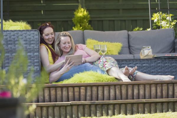affectionate lesbian couple using digital tablet