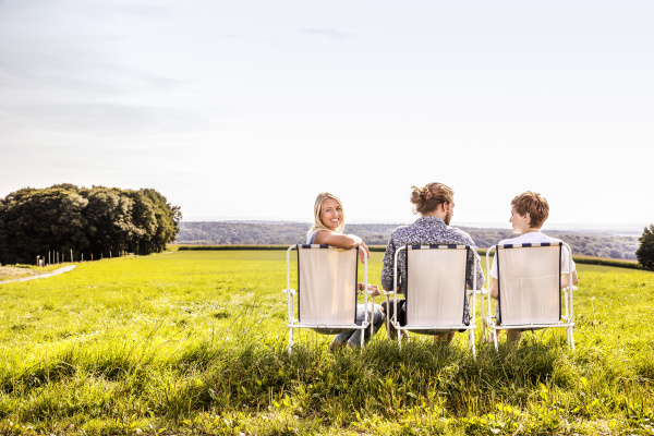 friends sitting on camping chairs in