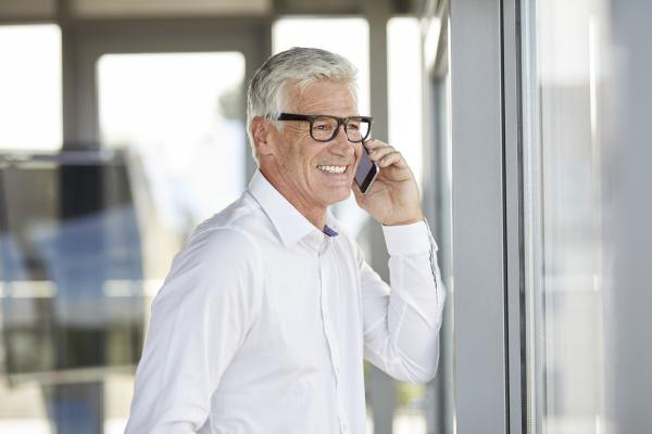 successful businessman using smartphone talking on