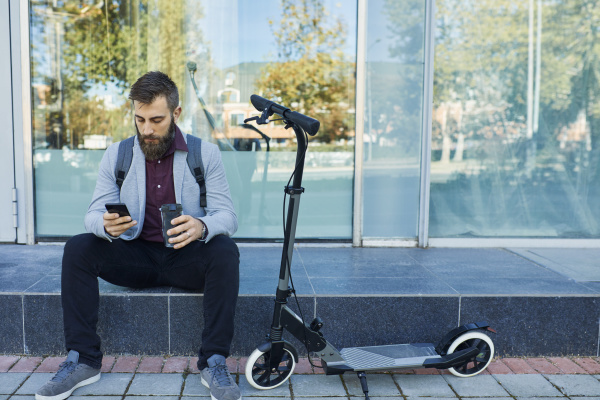 businessman sitting outdoors using cell phone