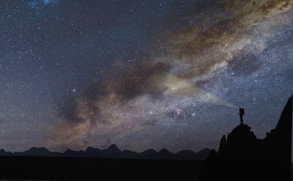 silhouette of rocks under starscape in