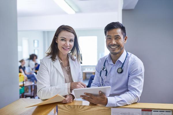 portrait confident doctors with digital tablet