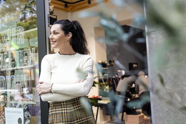 shop owner standing in door of