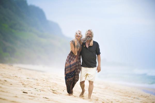 happy senior hippie couple strolling side