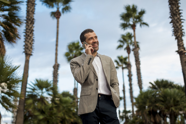 happy businessman talking on cell phone