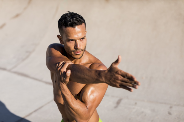 barechested muscular man doing stretching exercise