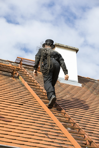 chimney sweep climbing up house roof