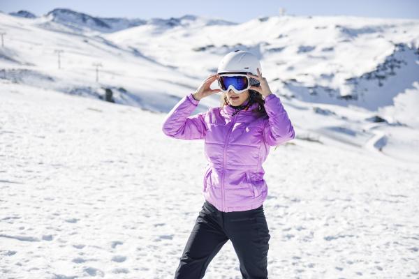 woman wearing ski clothing getting ready