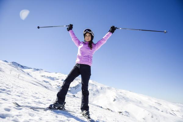 happy woman raising her ski poles