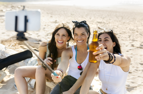 happy female friends with beer bottles
