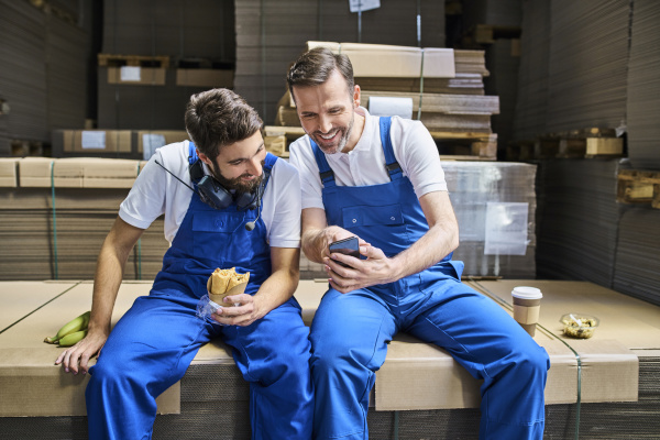 two happy workers using cell phone
