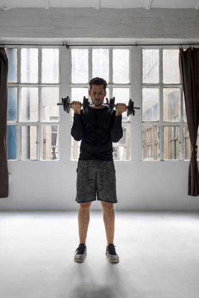 mature man doing dumbell training in