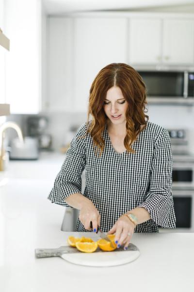 woman slicing orange in kitchen